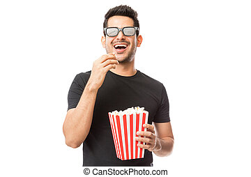 Smiling Young Man Watching 3D Movie While Eating Popcorn