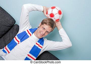 Smiling young man watching football