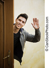 Smiling young man waving at the camera with a friendly cheerful smile as he peers around the edge of a wooden door
