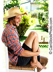 Smiling young man wearing cowboy hat outside