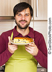 Smiling young man with apron holding a plate with homemade cake in his kitchen