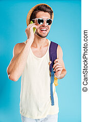 Smiling young man with backpack talking on cell phone