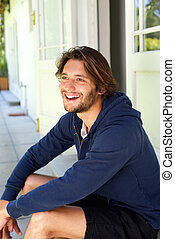 Smiling young man with beard sitting on patio in summer