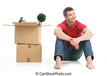 Smiling young man with cardboard box and looking up. Happy...