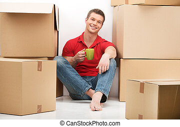 Smiling young man with cardboard box drinking tea. Happy...