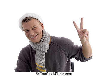 smiling young man with christmas hat showing two fingers