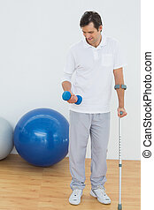 Smiling young man with crutch and dumbbell