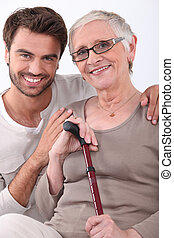 Smiling young man with his arms around a senior woman in...