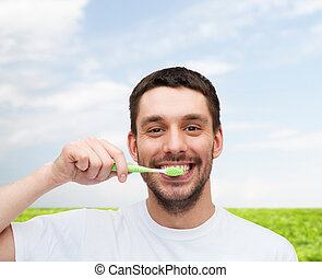 smiling young man with toothbrush - health and beauty...