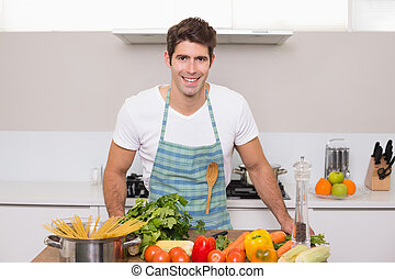 Smiling young man with vegetables standing in kitchen