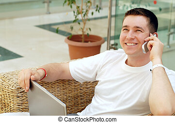Smiling young man working on laptop computer and call by phone at home
