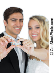 Smiling young married couple holding their wedding rings