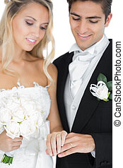 Smiling young married couple wearing wedding rings