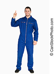 Smiling young mechanic in boiler suit pointing up