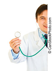 Smiling young medical doctor holding up stethoscope isolated on white. Close-up.