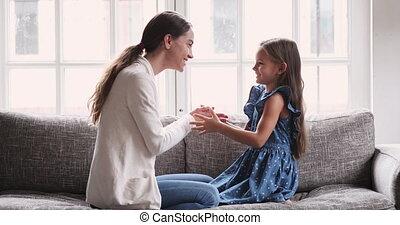Smiling young mixed race mother playing hand game with daughter.