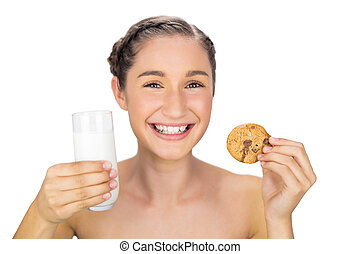 Smiling young model holding cookie and milk