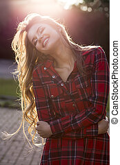 Smiling young model with long lush hair posing at the street in rays of sun