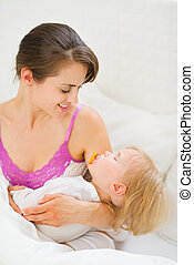 Smiling young mother holding sleeping baby
