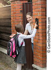 Smiling young mother opening door to her daughter that came from school
