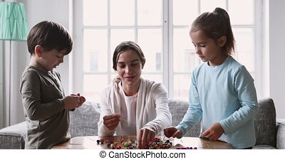 Smiling young mum babysitter and two kids play sensory game...