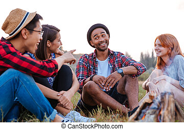 Smiling young people sitting and talking near bonfire -...