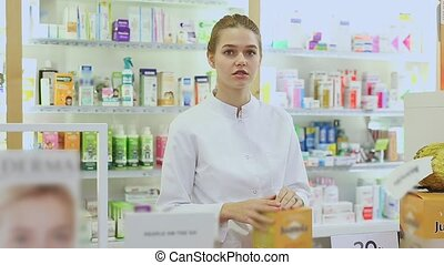 Cheerful female pharmacist demonstrating assortment of pharmacy