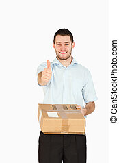 Smiling young post employee handing over parcel while giving thumb up against a white background