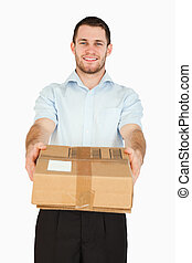 Smiling young post employee handing over parcel against a...
