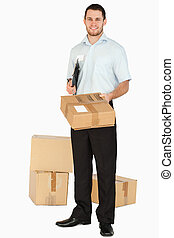 Smiling young post employee with clipboard handing over parcel