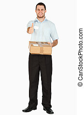 Smiling young post employee with parcel giving thumb up