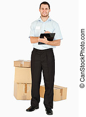 Smiling young post employee with parcels and clipboard...