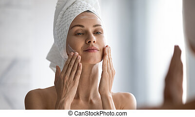 Closeup head shot pleasant beautiful woman applying moisturizing creme on face after shower. Smiling young pretty lady wrapped in towel smoothing perfecting skin, daily morning routine concept.