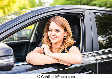 Smiling young pretty woman in the black car. Concept of travel