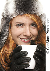 smiling young redhead woman in winter dress holding coffee cup on white background