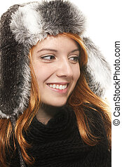 smiling young redhead woman in winter dress looking on side on white background