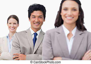 Smiling young sales team with folded arms against a white ...