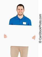 Smiling young salesman holding banner against a white...