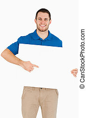 Smiling young salesman pointing at banner in his hands