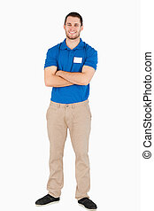 Smiling young salesman with arms folded against a white...