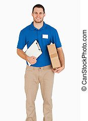 Smiling young salesman with packet and clipboard against a...