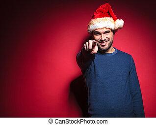 Smiling young santa pointing at you