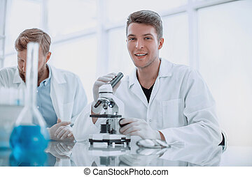 smiling young scientist using microscope for research.