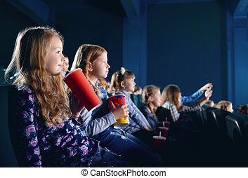 Smiling young spectators eating popcorn and watching cartoon in cinema.