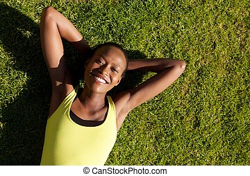 Smiling young sports woman relaxing on grass