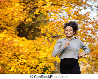 Smiling young sports woman running outdoors