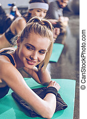 Smiling young sportswoman lying on yoga mat and looking away while exercising at the gym