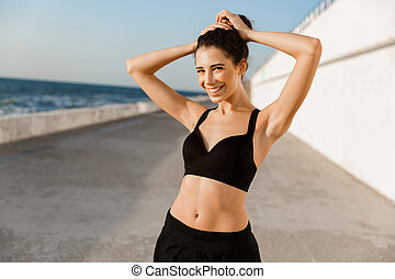 Smiling young sportswoman standing outdoors