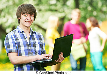 smiling young student boy with laptop