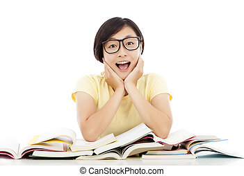 smiling young student girl thinking with book on the desk